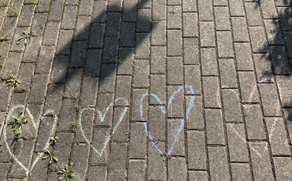 4 gezeichnete Herzchen auf dem Boden. Neljä piirrettyä sydäntä katukiveyksellä